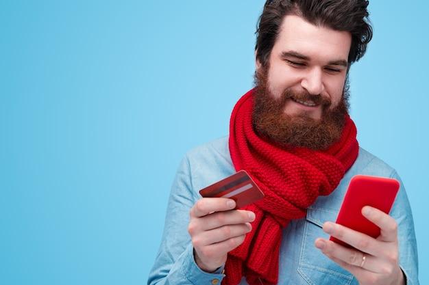 Retrato, de, joven, hombre barbudo, tenencia, tarjeta de crédito, y, teléfono móvil