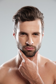 Retrato de un joven hombre desnudo sexy tocando la barbilla