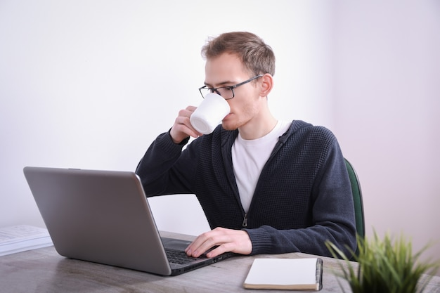 Retrato de joven hombre de negocios sentado en su escritorio, la tecnología portátil de escritorio en la oficina. marketing en internet, finanzas, concepto de negocio