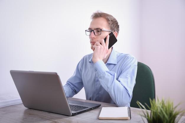 Retrato de joven hombre de negocios sentado en su escritorio con tecnología portátil en la oficina. marketing en internet, finanzas, concepto de negocio