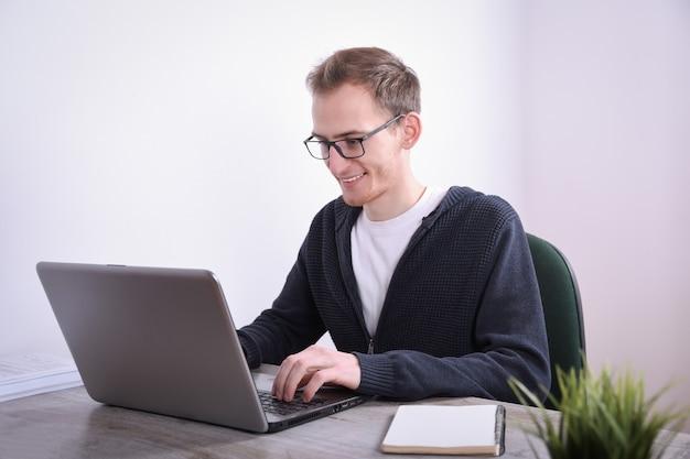 Retrato, de, joven, hombre de negocios, sentado, en, el suyo, escritorio, computadora de escritorio, computadora portátil, tecnología, en la oficina., marketing en internet, finanzas, concepto empresarial