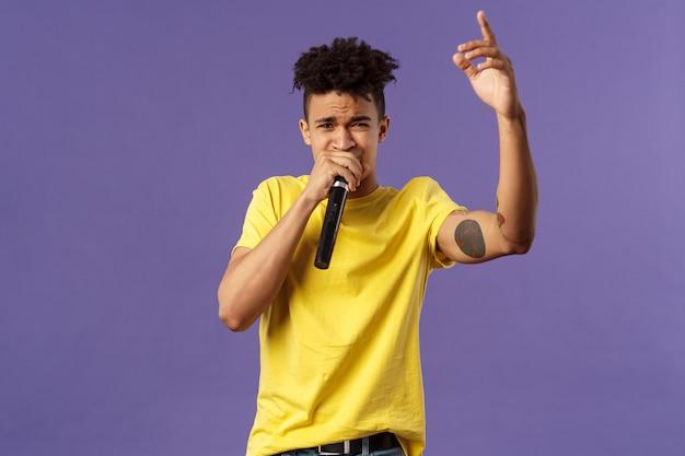 Retrato de un joven inconformista descarado y despreocupado con tatuajes, camiseta amarilla actuando frente al público con su hip-hop o rap, cantando una canción, levantando el dedo, sostenga el micrófono, karaoke
