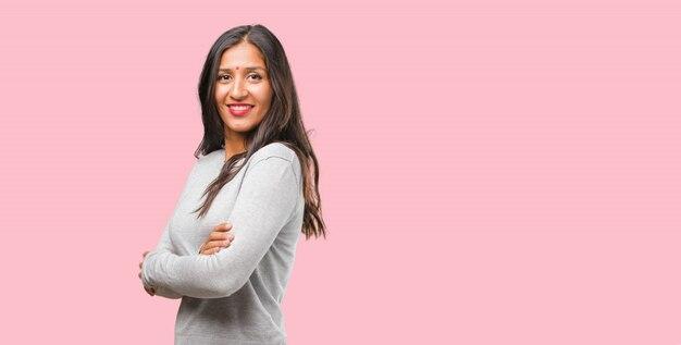 Retrato de una joven india que cruza sus brazos, sonriente y feliz, confiada y amigable