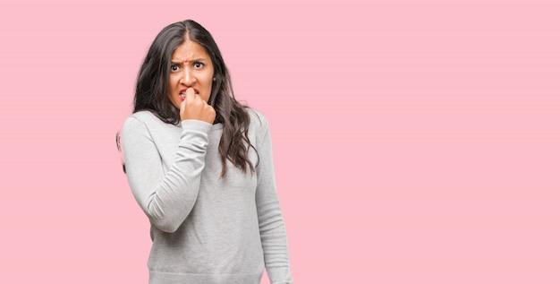 Retrato de una joven india que se muerde las uñas, nerviosa y muy ansiosa y asustada por el futuro, siente pánico y estrés.