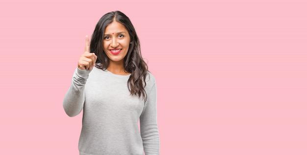 Retrato de una joven india que muestra el número uno, símbolo de contar, concepto de matemáticas, confiado y alegre
