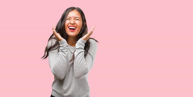 Retrato de una joven india riendo y divirtiéndose, relajada y alegre