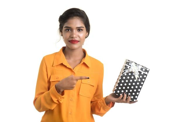 Retrato de joven india sonriente feliz con cajas de regalo en una pared blanca.