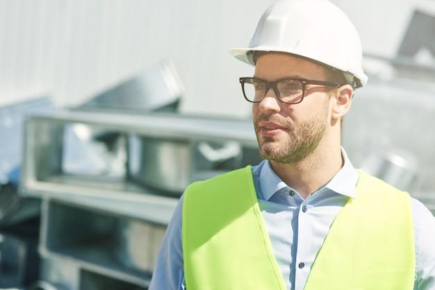 Retrato de joven ingeniero civil con casco mirando a otro lado mientras está de pie en el sitio de construcción