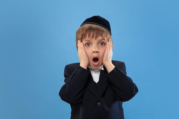 Retrato de un joven judío ortodoxo aislado en estudio azul