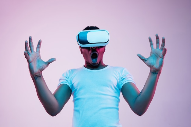 Retrato de joven jugando en gafas de realidad virtual en luz de neón