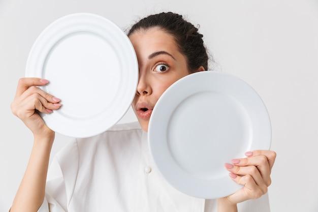 Retrato de una joven juguetona lavando platos