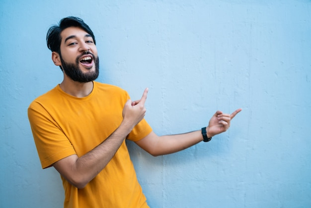 Retrato de joven latino apuntando y mostrando algo sobre fondo azul.