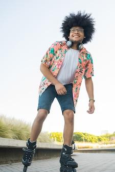 Retrato de joven latino disfrutando y divirtiéndose mientras patina al aire libre en la calle. concepto deportivo. concepto urbano.