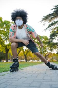 Retrato de joven latino con mascarilla mientras patina al aire libre en la calle