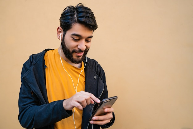 Retrato de joven latino usando su teléfono móvil con auriculares contra el espacio amarillo. concepto de comunicación.
