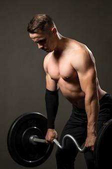 Retrato joven levantamiento de pesas en el gimnasio
