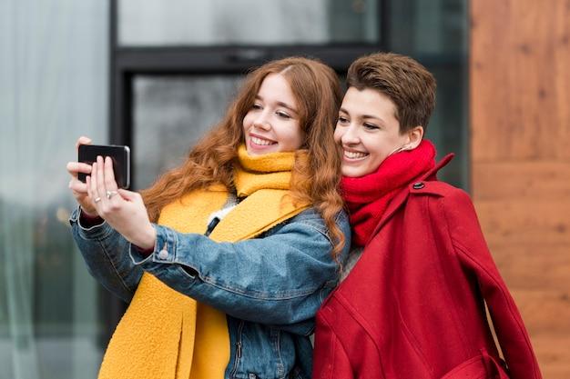 Retrato de joven linda tomando una foto juntos