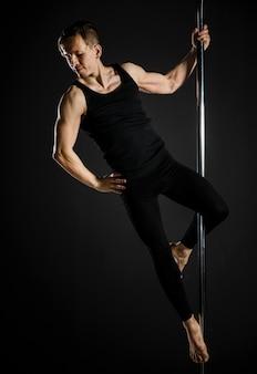 Retrato de joven macho haciendo un pole dance
