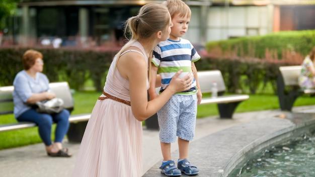 Retrato de joven madre acariciando y calmando a su hijo pequeño llorando en el parque