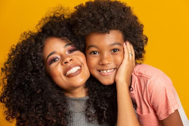 Retrato de joven madre afroamericana con el hijo del niño. pared amarilla familia brasileña.