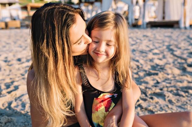 Retrato de joven madre atractiva con hermosa hija vestida con trajes de baño negros en la playa de verano de cerca