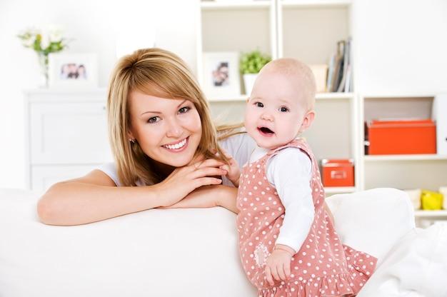 Retrato de joven madre feliz con bebé recién nacido en casa