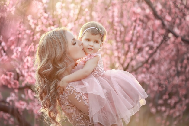 Retrato de joven madre hermosa con su pequeña hija. todavía cerca de la familia amorosa. mujer atractiva que detiene a su niño en flores rosadas y sonriente