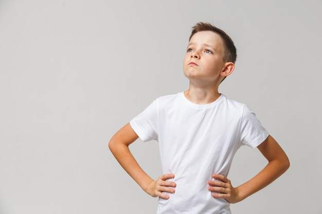 Retrato de joven con las manos en la cintura, levantando la cabeza sobre fondo blanco.