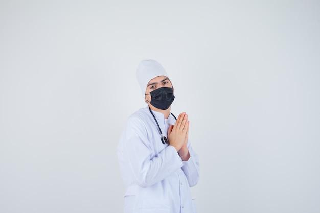Retrato de joven manteniendo las manos en gesto de oración en uniforme blanco, máscara y mirando esperanzado vista frontal