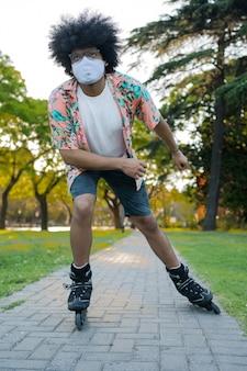 Retrato de joven con mascarilla mientras patina al aire libre en la calle
