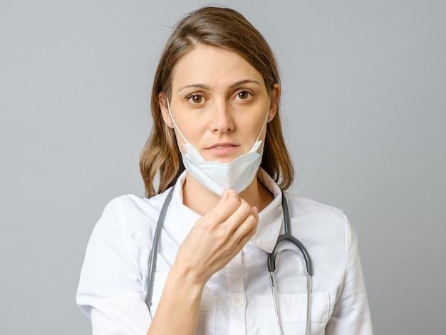 Retrato de joven médico cansado quitándose la mascarilla médica