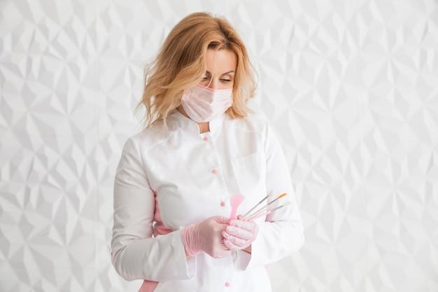Retrato de joven médico esteticista atractivo con pincel en mano y míralo. cosmetóloga con herramientas médicas. clínica de belleza u hospital.