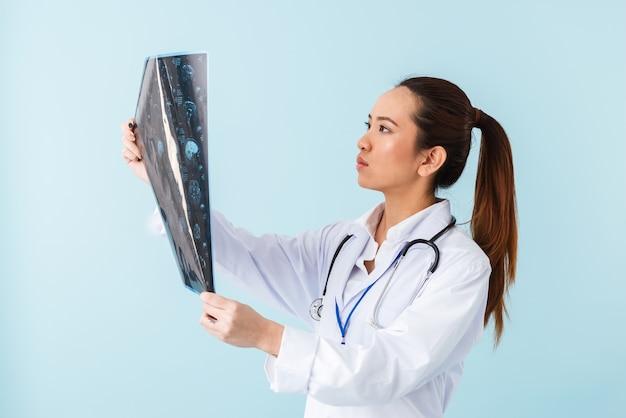 Retrato de una joven médico mujer concentrada posando aislada sobre pared azul con rayos x.