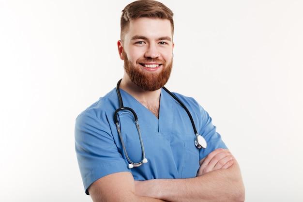 Retrato de un joven médico sonriente con estetoscopio de pie con los brazos cruzados