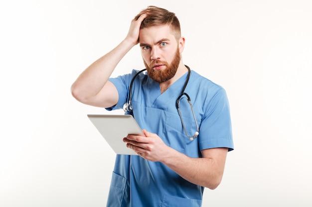 Retrato de un joven médico sorprendido en uniforme azul