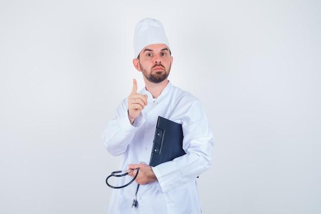 Retrato de joven médico sosteniendo portapapeles, estetoscopio, apuntando hacia arriba en uniforme blanco y mirando inteligente vista frontal