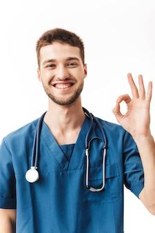 Retrato de joven médico varón alegre en uniforme con fonendoscopio en el cuello mostrando feliz gesto ok mientras