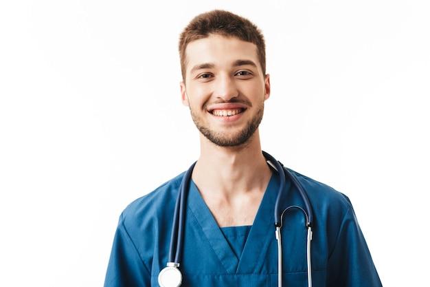 Retrato de joven médico varón sonriente en uniforme con fonendoscopio en el cuello felizmente