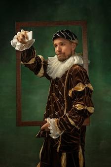 Retrato de joven medieval en ropa vintage con marco de madera en la pared oscura