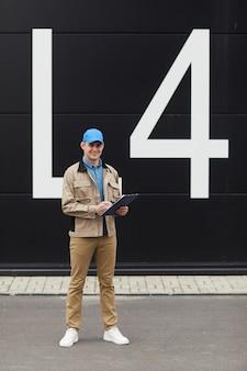 Retrato de joven mensajero haciendo notas en el documento mientras está de pie al aire libre