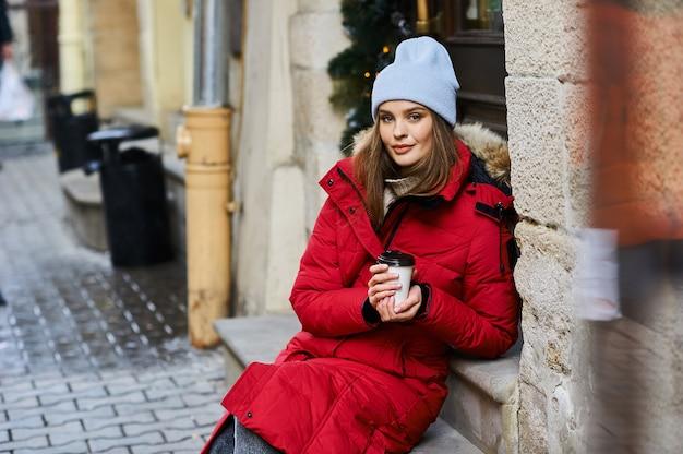 Retrato de una joven moda caminando por la calle de la ciudad en época de invierno