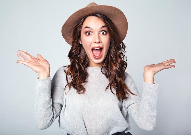 Retrato de joven modelo elegante con expresión facial de sorpresa en gris