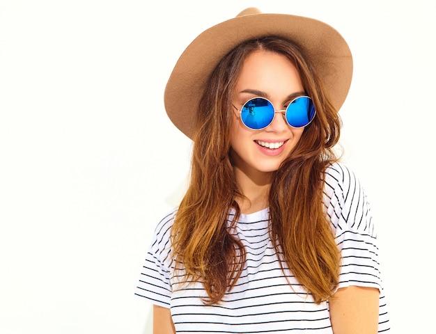 Retrato de joven modelo elegante mujer riendo en ropa casual de verano en sombrero marrón aislado en la pared blanca