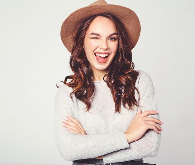 Retrato de joven modelo elegante riendo en ropa casual gris de verano en sombrero marrón con maquillaje natural