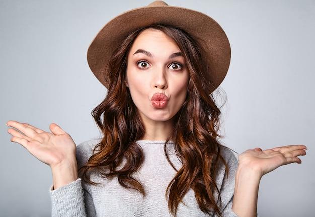 Retrato de joven modelo elegante riendo en ropa casual gris de verano en sombrero marrón