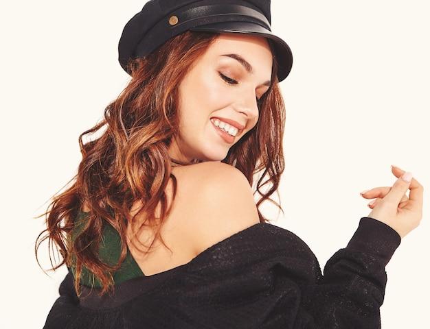 Retrato de joven modelo elegante riendo en ropa casual de verano negro en gorra con maquillaje natural en blanco