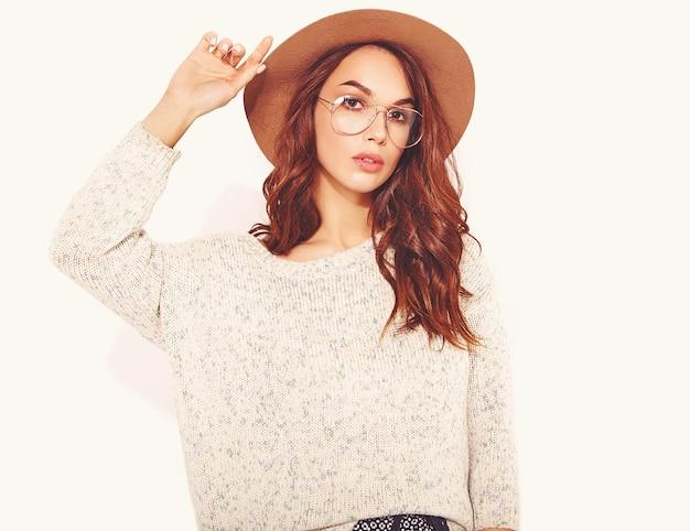 Retrato de joven modelo elegante en ropa casual de verano en sombrero marrón con maquillaje natural en gafas en blanco