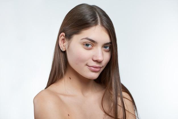Retrato de una joven modelo hermosa sin maquillaje en su rostro