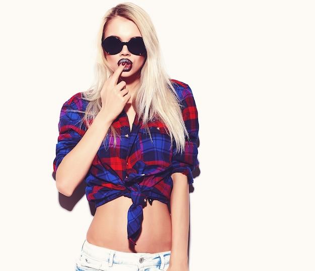 Retrato de joven modelo de mujer feliz con maquillaje brillante y labios coloridos en ropa de verano hipster aislado en blanco. enloqueciendo y tocando sus labios