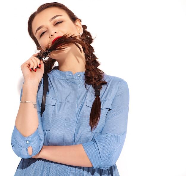 Retrato de joven modelo de mujer sonriente feliz con maquillaje brillante y labios rojos con dos coletas en las manos en el colorido vestido azul de verano